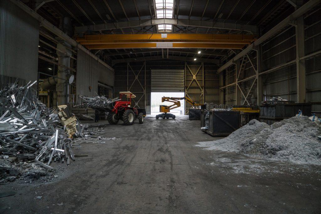 Heap of aluminium parts in scrap yard, horizontal composition,